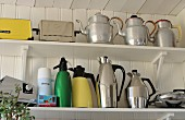 Collection of metal kettles, thermos flasks and retro toasters on white shelves mounted on wooden wall