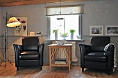 Two black leather armchair flanking delicate wooden table in comfortable, Scandinavian, country-house interior