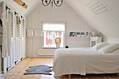 Simple, white, country-house bedroom in attic with fitted wardrobes, plain wooden floor and Scandinavian vintage ambiance
