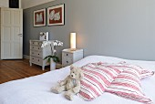 Teddy bear and striped scatter cushions on double bed against grey-painted wall; country-house-style chests of drawers in background