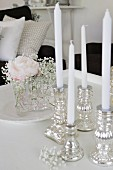 White candles in silver candlesticks and posy of rose and gypsophila