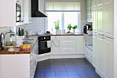 White, country-house kitchen with L-shaped counter and dark tiled floor