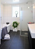 White bathroom with glazed shower cabinet, dark tiled floor and house plant below window in background