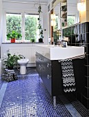 Washstand with black base unit and fitted mirrored cabinets in narrow bathroom with bidet