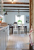 Blue from kitchen to dining area below chandelier hanging from wood-beamed ceiling