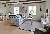 Essplatz und Sitzbereich mit Sofa im offenen Wohnraum mit Holzwänden und sichtbaren Deckenbalken