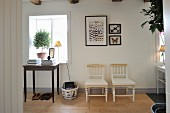 Table in front of window with plant on windowsill next to framed and mounted butterflies above pair of chairs