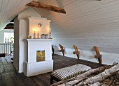 Lit candles on mantelpiece in attic bedroom with white, wood-clad walls