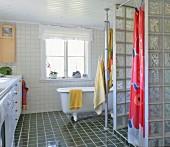 Shower area with glass brick walls, vintage bathtub in background on dark tiled floor