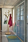 Rustic foyer with double front door and stylised tree as coat stand