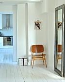 Minimalistisch möblierter Flurbereich mit Wandspiegel und Holzstuhl auf weißem Dielenboden