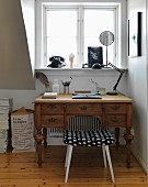 Vintage desk and vintage stool below window with rotary dial telephone on windowsill