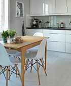 Elegant, white kitchen counter, vintage kitchen table and Eames chairs in renovated country house