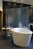 Pleasant bathroom with dark tiles, tray table and candelabra next to free-standing bathtub