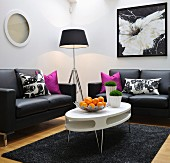 Lounge area with white, oval, retro table and simple, black leather sofas