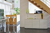 Sideboard under staircase; kitchen island with bar stools to one side