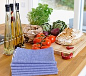 Stacked napkins and oil bottles next to fresh vegetables and bread on island counter with pale wooden worksurface