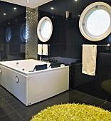 Bullaugenfenster hinter Whirlpoolwanne in dunkel gefliestem Badezimmer