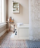 Candlesticks on steps leading to bathtub and ornamental tiled floor in traditional bathroom