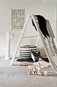Leiterartiges Gestell mit aufgehängtem Fell und Tuch, Holz Bauklötze und schwarz weisser Polsterhocker auf Estrichboden in loftartigem Raum