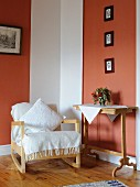 Pale, Scandinavian rocking chair, vintage console table and framed photos of children on terracotta wall panels in comfortable reading corner