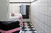 View of free-standing bathtub and colour-coordinated towels in black and white tiled bathroom
