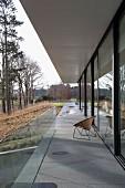 Retro Stuhl auf Terrassenstreifen aus Beton vor zeitgenössischem modernem Wohnhaus, in herbstlicher Landschaft