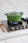 Green enamel pan on gas hob and marble worksurface