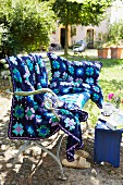 A crocheted blue blanket and cushion cover with a floral pattern on an antique bench in a garden