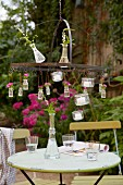 A vase of flowers and tealights hanging from an outdoor chandelier above a bistro table in a garden