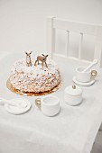 Nut cake decorated with icing sugar and animal figurines on child's table with dolls' tea set