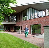 Terrace in back garden of Belgian, architect-designed house with brick facade, large windows and protruding concrete roof; man with watering can in foreground