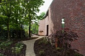 Meandering garden path along mainly solid brick facade of modern Belgian house