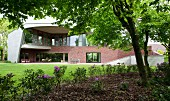 Idiosyncratic house with enclosing concrete facade, glass upper walls and brick-clad lower storey facing park-like gardens