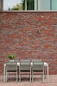 Simple, modern outdoor dining area against brick facade with glazed upper storey