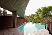 Concrete roof with Expressionist form over sun terrace of polygonal swimming pool