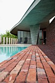 Brick-paved edge of pool below curved concrete roof in classical modernist style