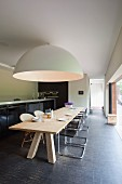 Long, pale wooden table and classic cantilever chairs below gigantic hemispherical lamp; kitchen base units with black doors