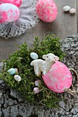 Easter arrangement of bark, moss, sugar eggs and china lamb