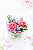 Vase with posy of pink carnations and forget-me-nots on embroidered tablecloth