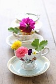 Three demitasse cups with various flowers