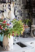 Vintage jug of flowers on kitchen worksurface in front of kitchen utensils hung on wall tiled with blue and white patterned, old-fashioned tiles