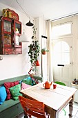 Small, cheerful kitchen-dining room with colourful chairs at antique wooden table and vintage, wall-mounted cabinet above storage bench with scatter cushions