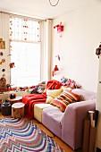 Rot- und Pinktöne in Sofaecke mit Baumstammtischen und Webteppich, Nippes, indischen Souvenirs und Kuckucksuhr