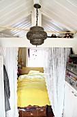 Eingebautes Bett mit Spitzenvorhang, davor orientalische Hängeleuchte und Aufbewahrung in Vintage Koffern