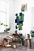 Wand-Collage aus Stoffresten in Grüntönen und Kleinmöbel in skandinavischer Altbauwohnung