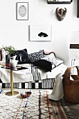 Sofa with blankets and hand-made, black and white scatter cushions on pale, patterned woollen rug