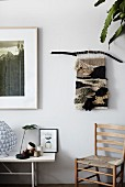 Hand-woven wall hanging in natural shades above rush-bottom chair next to ornaments on table
