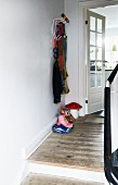 Eames Hang-It-All coat rack in renovated foyer with plain wooden floor