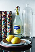 Glass swing-top bottle, colourful, rolled place mats, retro glass carafe and yellow lemons on black granite kitchen worksurface